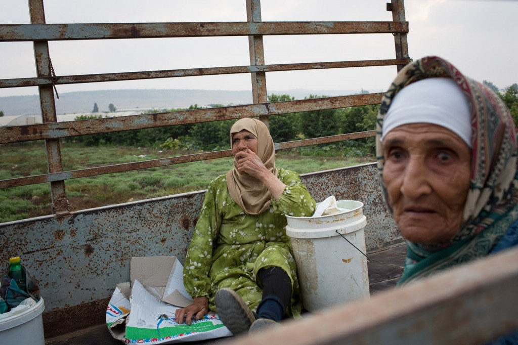 Falama, Palestine - 04/08/2015: Two women wait patiently in their farm vehicle for Israel to open the separation barrier to allow them access to their farmland. There are only three half hour openings per day and 300 farmers queueing for access, some denied entry on a dally basis.