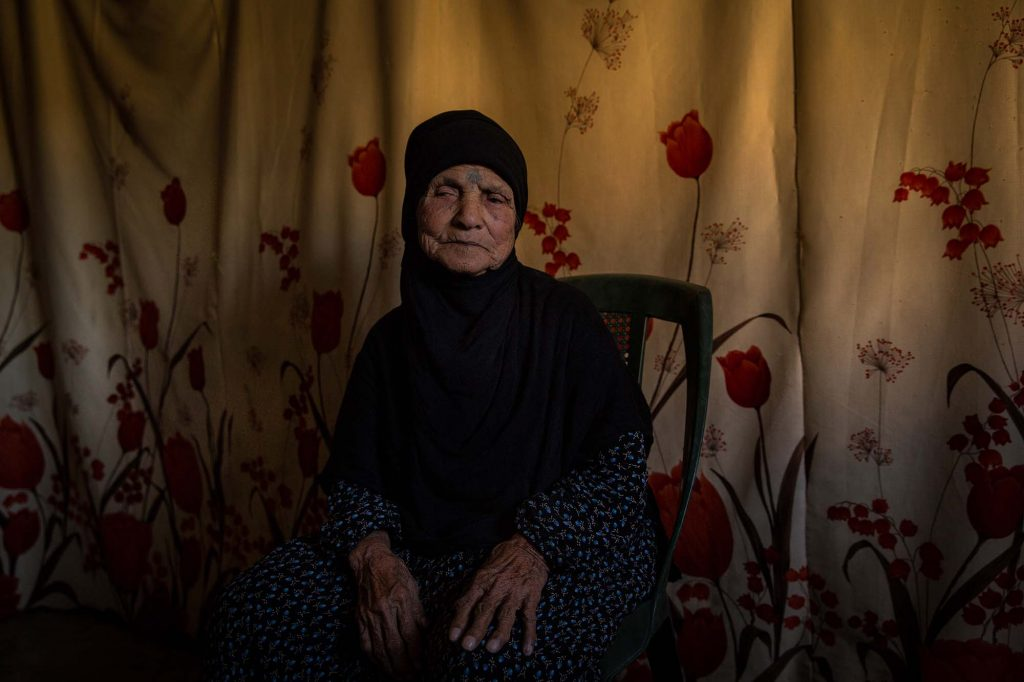 "Bekaa Valley, Lebanon - 15/10/2016: 85 years old Sharifi had tattoos produced on her hands and face when she was 10. The Dom used to be famous for this but the new generation no longer practices this tradition. In Syria she lived in a tent with no chairs and moved into a concrete home when she was married at 15 years of age. She speaks Domari and is now living in a tented settlement in the Bekaa valley: ""We had everything in Syria, now we have nothing. We are happy."""